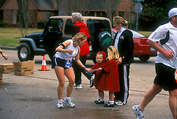 Stock photo of a woman's young daughters helping her get ready to start the marathon