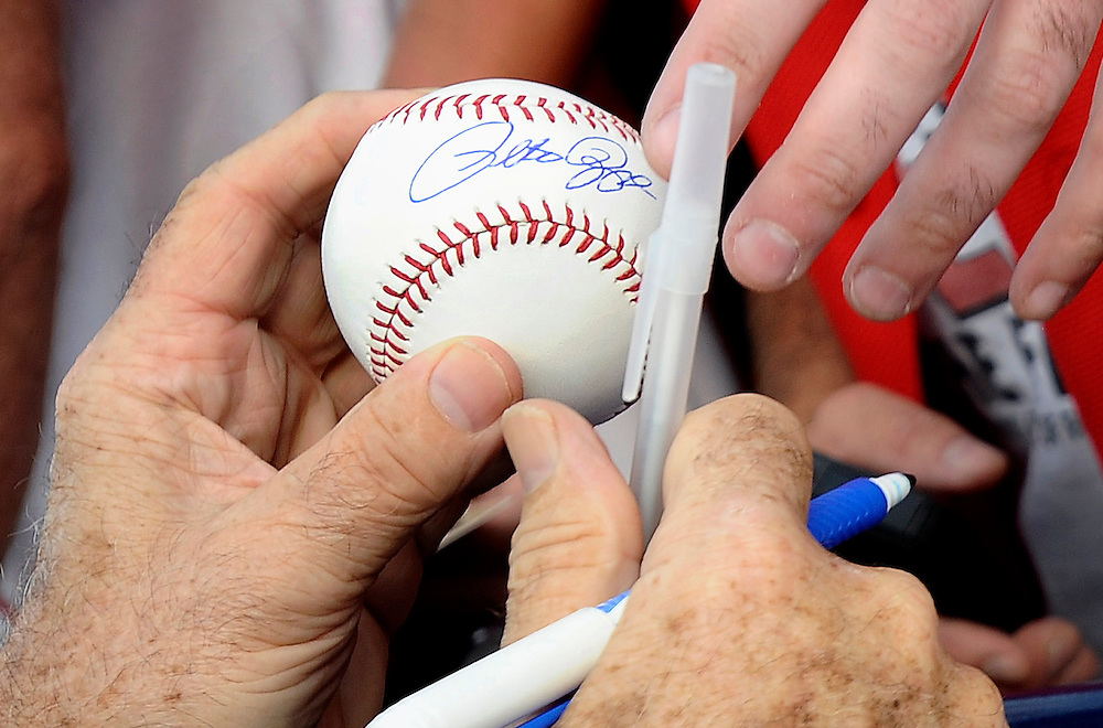 Pete Rose hands back a ball he autographed to a fan at The Ballpark at Harbor Yard, Monday, June 16, 2014, in Bridgeport, Conn. Rose, banned from Major League Baseball, returned to the dugout for one day to manage the independent minor-league Bridgeport Bluefish. (AP Photo/Jessica Hill)
