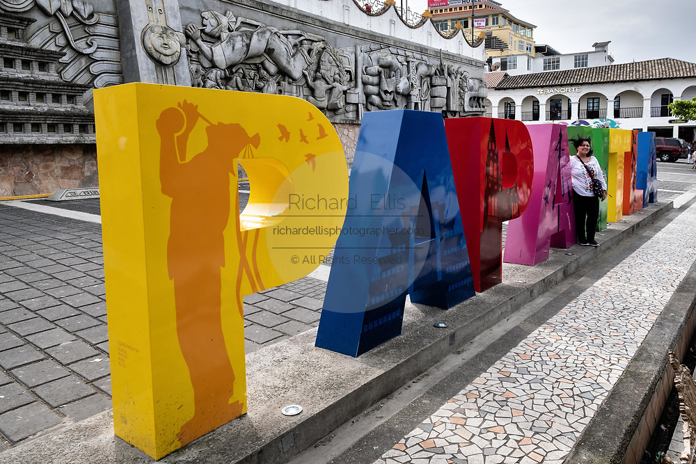 A poses at the city sign in front of the sculpture; Evolution of the Totonac culture by Teodoro Cano Garcia, in the Plaza Central Israel Tellez Park in Papantla, Veracruz, Mexico.