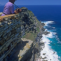 A traveler overlooks the Cape of Good Hope at the southern tip of Africa, where the Atlantic and Indian Oceans meet.
