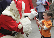 Middletown, New York - Santa helps a young boy unwrap a present at the Middletown YMCA on Dec. 4, 2010.