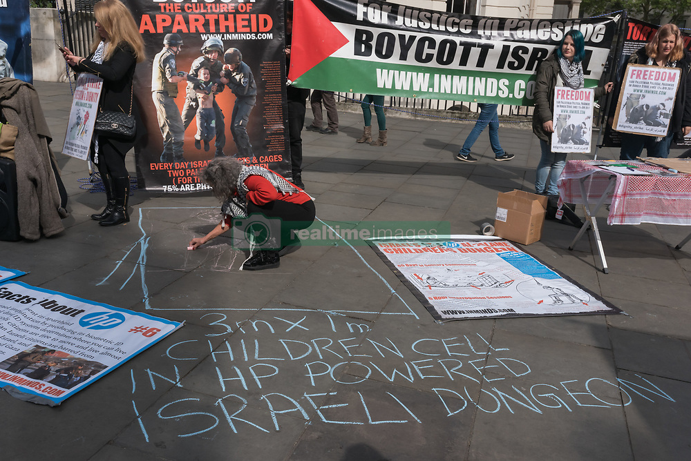 April 28, 2017 - London, UK - London, UK. 28th April 2017. A woman chalks a figure of a child showing the size of the underground cells they are kept in solitary confinnemnet in Israeli prisons, run using HP hardware and software. Tye vigil by Inminds human right group  on the edge of Trafalgar Square gave information and stood in solidarity with the largest hunger strike of Palestinian political prisoners in 5 years. Over 1500 Palestinian prisoners from all factions went on hunger strike on 17th April 2017 and more have joined since despite brutal attacks by prison guards and force feeding. They are demanding basic human rights and want all prisoners to be allowed family visits, the use of phones to contact family, proper health treatment without charges, humanitarian treatment during transfers between courts and prisons, an end to end to administrative detention and solitary confinement, to be allowed to receive clothing, books and hygiene products from their families and to run their kitchens rather than have to eat food prepared by Israeli criminal prisoners who in some prisons routinely spit and urinate in it. Peter Marshall Images Live (Credit Image: © Peter Marshall/ImagesLive via ZUMA Wire)