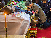 27 JANUARY 2014 - BANGKOK, THAILAND:  A woman prays during over the body of Suthin Taratin during the bathing rites for anti-government leader at Wat Sommanat Rajavaravihara in Bangkok. In Thai tradition, after death a bathing ceremony takes place in which relatives and friends pour water over one hand of the deceased. Suthin was a core leader of the People's Democratic Force to Overthrow Thaksinism (Pefot), one of several organizations leading protests against the elected government of Thai Prime Minister Yingluck Shinawatra. He was murdered Sunday, Jan. 28, while he was leading a rally to prevent voters from reaching a polling center in the Bang Na district of Bangkok.    PHOTO BY JACK KURTZ