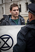 A male Extinction Rebellion protester speaking to a policeman at St Jamess Park on the 7th October 2019 in Central London in the United Kingdom. Extinction Rebellion protesters occupy locations across central London including Westminster Bridge, Whitehall and Trafalgar Square in a wave of protests planned to continue for 2 weeks.