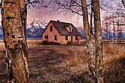 An artistic, morning image of one of the historic homesteads in Jackson Hole, WY with a moody, peach colored sky. The distant Grand compliments the layout. Textured with the feather pattern of a Great Gray Owl.