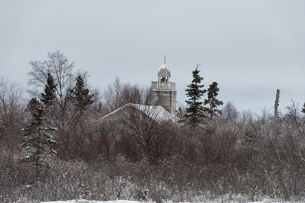 """On a bend in the meandering Kwethluk River, not far off the Bering Sea, five abandoned buildings rise above the alders. <br /> <br /> The Moravian Children's Home opened in 1926, three miles upriver from the village of Kwethluk, Alaska. Moravian missionaries founded the facility in an effort to provide care and education for children, most of whom were Alaska native and orphaned by epidemics which ravaged area villages.<br /> <br /> The facility was closed hastily due to a tuberculosis outbreak among the residents.<br /> <br /> Many of the children who lived at the orphanage are now elders living in communities throughout the Yukon-Kuskokwim Delta.<br /> <br /> Nunapitsinghak is the Yup'ik name of the original property on which the home was built, it means """"great, little land""""."""