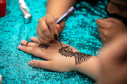 © Licensed to London News Pictures. 08/06/2019. London, UK. A woman applies a henna tattoo to another woman's hand at an event in Trafalgar Square to celebrate Eid ul-Fitr - the breaking of the fast. The festival marks the end of Ramadan, a holy month in the Muslim calendar when Muslims fast during the hours of daylight. This year, Eid occurred on Tuesday 4 June. Photo credit : Tom Nicholson/LNP