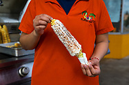 Elizabeth Morales holding Corn on the cob roasted street side and served with mayonnaise, cheese and chili at El Mercadito snack shop in downtown Woodburn, Oregon