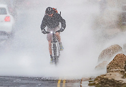 © Licensed to London News Pictures. 08/02/2019. Southsea, UK. A cyclist gets a soaking as the wind brings  waves crashing across the road at Southsea, near Portsmouth. Storm Erik is hitting southern parts of the UK. Photo credit: Peter Macdiarmid/LNP