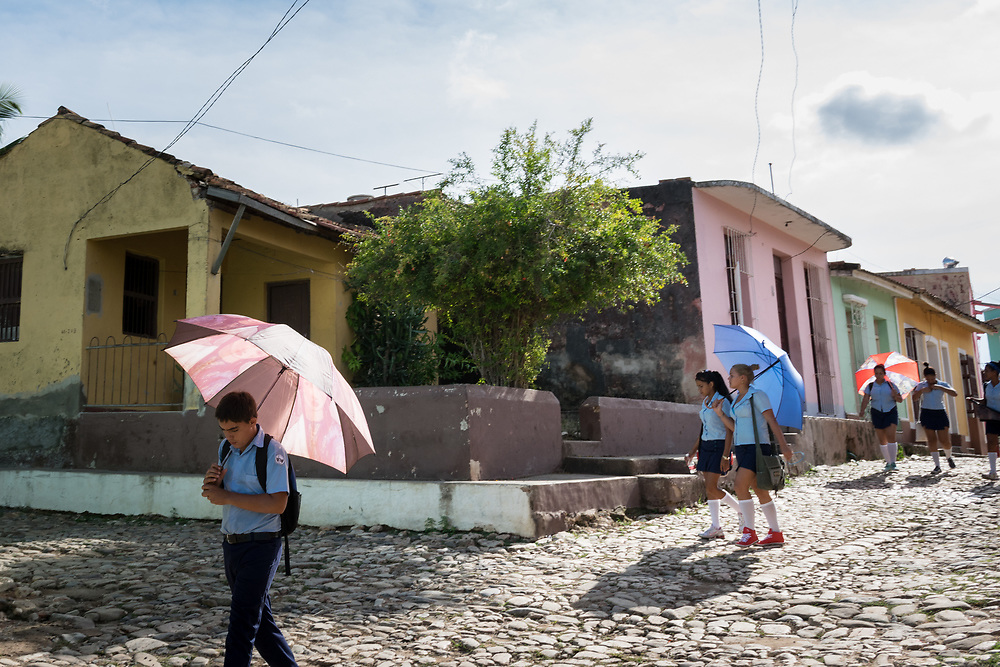 24 September 2015, Trinidad, Cuba: Children walk home from school, using umbrellas as protection from the strong, midday sun.