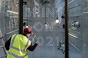 After a bleak year of Coronavirus pandemic misery, a contractor applies stars to window glass in Harvey Nichols's Christmas-themed window which urges Londoners to be optimistic for the coming year, on 13th November 2020, in London, England.