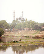Small boat crossing Gomti River in front of the Great Imambara, Lucknow, Uttar Pradesh, India