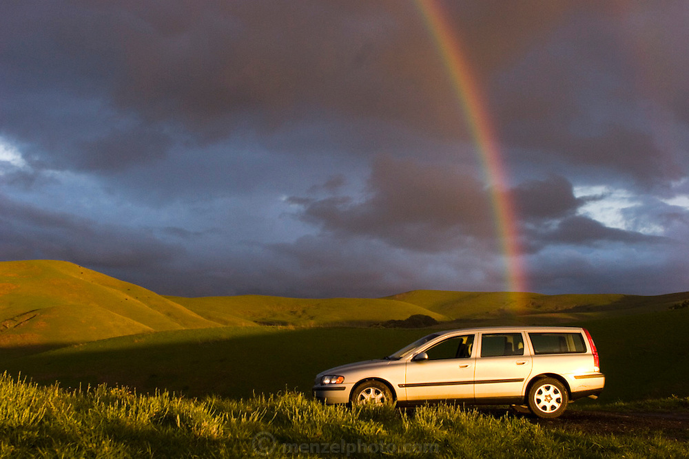 Rainbow on a winter afternoon over vineyards in the southern part of the Napa Valley, California. The photographer's 2001 Volvo station wagon is at the end of the rainbow.