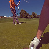 Chad Jones & Lindsey Mitchell putt on a green at Big Sky Golf Course in Big Sky, Montana.