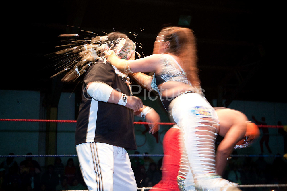 Female wrestler throwing a foam custard pie in referees face. Lucha Libre wrestling origniated in Mexico, but is popular in other latin Amercian countries, including in La Paz / El Alto, Bolivia. Male and female fighters participate in the theatrical staged fights to an adoring crowd of locals and foreigners alike.