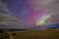 The aurora borealis turns the sky purple and green over Frenchtown, Montana. Passing clouds were hiding part of the northern lights.