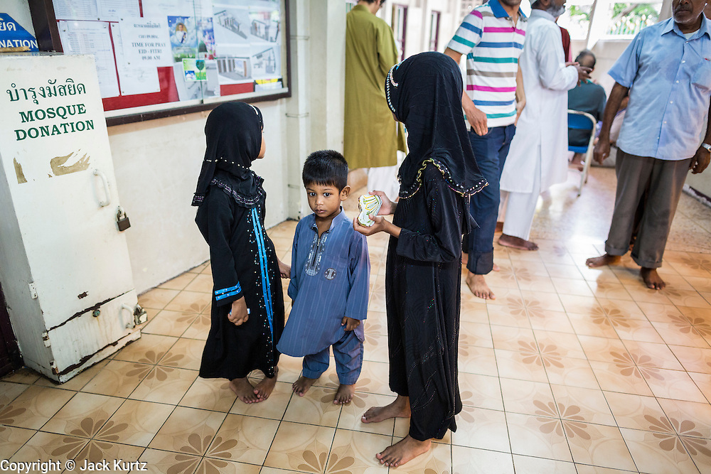 """08 AUGUST 2013 - BANGKOK, THAILAND:Children wait for their father before Eid al-Fitr services in the entry way of Haroon Mosque in Bangkok. Eid al-Fitr is the """"festival of breaking of the fast,"""" it's also called the Lesser Eid. It's an important religious holiday celebrated by Muslims worldwide that marks the end of Ramadan, the Islamic holy month of fasting. The religious Eid is a single day and Muslims are not permitted to fast that day. The holiday celebrates the conclusion of the 29 or 30 days of dawn-to-sunset fasting during the entire month of Ramadan. This is a day when Muslims around the world show a common goal of unity. The date for the start of any lunar Hijri month varies based on the observation of new moon by local religious authorities, so the exact day of celebration varies by locality.       PHOTO BY JACK KURTZ"""