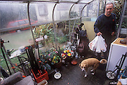 (MODEL RELEASED IMAGE). Mark Bainton brings the groceries for the upcoming photo shoot inside his Collingbourne Ducis, Wiltshire, England home. His dog Polo helps keep an eye on the process. (Supporting image from the project Hungry Planet: What the World Eats.)