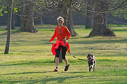 ©Licensed to London News Pictures 08/04/2020  <br /> Greenwich, UK. A lady running with her dog. People get out of the house from Coronavirus lockdown to exercise and enjoy the sunny weather in Greenwich park,Greenwich, London. Photo credit:Grant Falvey/LNP