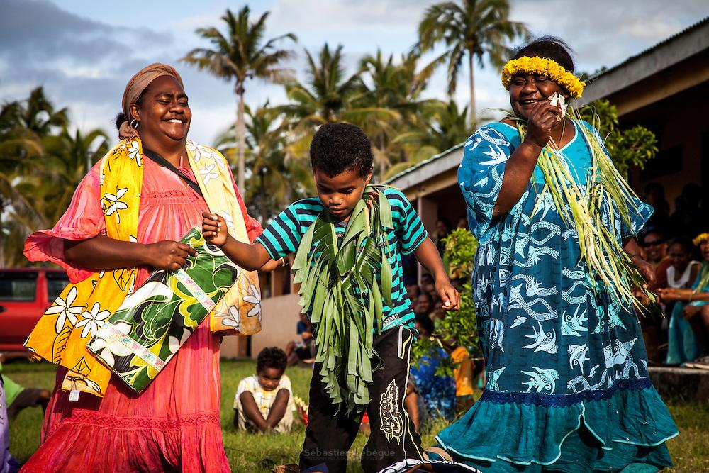 Échanges coutumiers lors d'une danse d'entrée du clan de la femme chez le clan de l'homme. Les jeunes garçons ou les jeunes filles font leur démonstration de danse face à l'autre clan. Les adultes, ou parfois des jeunes, les rejoignent dans cette danse en leur offrant des étoffes et de l'argent. C'est le tout premier contact entre les clans amorçant le tissage de leur lien.<br /> Cérémonie coutumière de mariage – Huiwatrul, Grande chefferie de Lössi, Lifou, Îles Loyauté, Nouvelle-Calédonie - Avril 2014