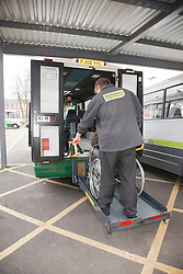 Rear view of bus driver on tailgate of specialised vehicle helping visually-impaired wheelchair user at a resource for people with physical and sensory impairment.