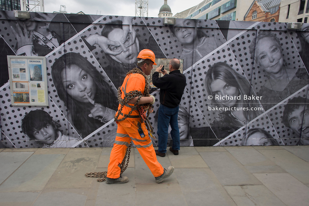 As a workman carries heavy chains along the street, a curious man looks through the aperture of a construction site window with a hoarding of many faces.
