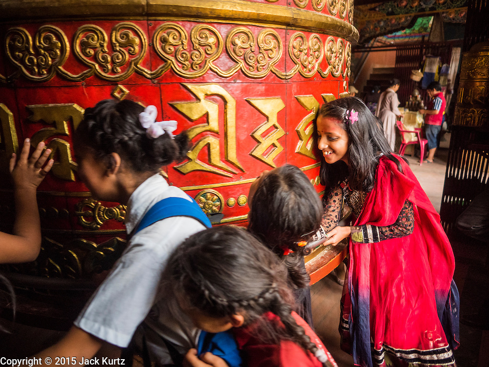 31 JULY 2015 - KATHMANDU, NEPAL:  School children spin a prayer wheel in a Tibetan monastery near Bodhnath Stupa. Bodhnath Stupa in the Bouda section of Kathmandu is one of the most revered and oldest Buddhist stupas in Nepal. The area has emerged as the center of the Tibetan refugee community in Kathmandu. On full moon nights thousands of Nepali and Tibetan Buddhists come to the stupa and participate in processions around the stupa. The stupa was heavily damaged in the earthquake of 25 April 2015 and people are no longer allowed to climb on the stupa, now they walk around the base and pray with butter lamps.   PHOTO BY JACK KURTZ