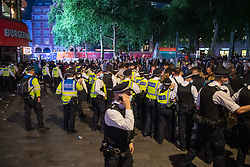 © Licensed to London News Pictures. 03/07/2021. London, UK. Police form a cordon in Leicester Square in central London after football fans gathered to celebrate England's EURO2020 quarter-final football win against Ukraine, when police moved in to clear the crowd they clashed with fans and were pelted with bottles, police detained several people. Photo credit: Peter Manning/LNP