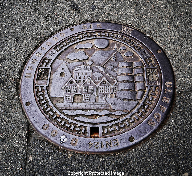 Bergen, Norway, 6/13/18. Distinctive man hole covers at the wharf area on the UNESCO listed Bergen Wharf.  Bergen, the second largest city in Norway.<br /><br />Photo by Dennis Brack