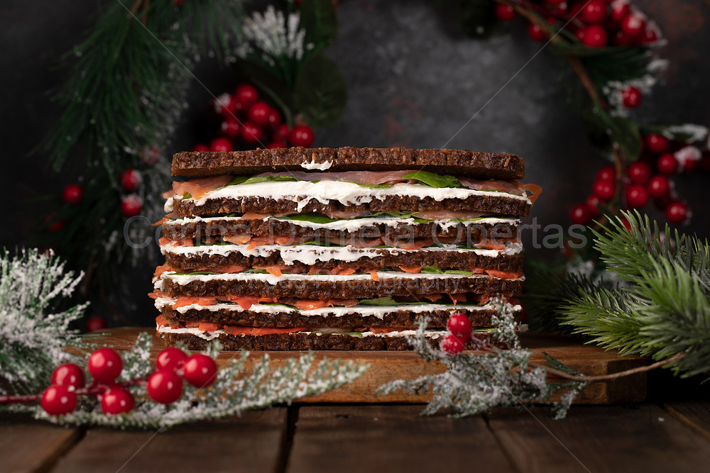 Salmon cake composed of several alternating layers of rye bread, cream cheese, slices of smoked salmon and spinach leaves, decorated for Christmas.