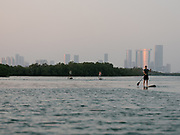 Kayakers enjoy an evening paddle. View towards Abu Dhabi skyline from the Mangrove National Park, one of the Emirate's most important ecological asset.