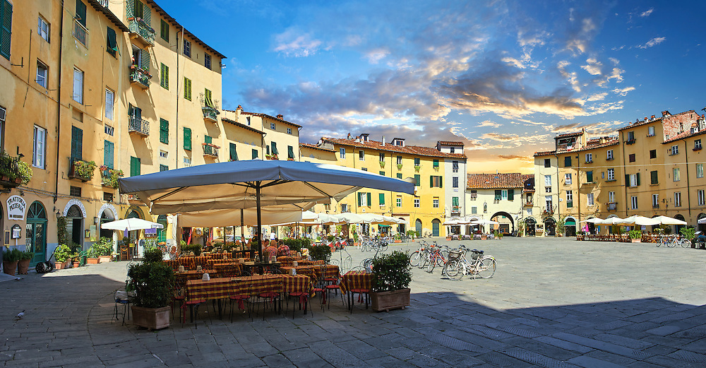 Outdoor cafe's in the Piazza dell'Anfiteatro inside the ancinet Roman ampitheatre of Lucca, Tunscany, Italy . Piazza dell'Anfiteatro is a public square in the northeast quadrant of walled center of Lucca. The ring of buildings surrounding the square, follows the elliptical shape of the former second century Roman amphitheater of Lucca. The square can be reached through four gateways located at the four vertices of the ellipse. A cross is carved into the central tile of the square with the arms pointing to the four gateways of the square. The base of the former amphitheater  dating back to the 1st or 2nd century BC, at its peak had about 18 rows of amphitheater seats held some 10,000 spectators.<br /> <br /> Visit our ITALY HISTORIC PLACES PHOTO COLLECTION for more   photos of Italy to download or buy as prints https://funkystock.photoshelter.com/gallery-collection/2b-Pictures-Images-of-Italy-Photos-of-Italian-Historic-Landmark-Sites/C0000qxA2zGFjd_k<br /> .<br /> <br /> Visit our ROMAN ART & HISTORIC SITES PHOTO COLLECTIONS for more photos to download or buy as wall art prints https://funkystock.photoshelter.com/gallery-collection/The-Romans-Art-Artefacts-Antiquities-Historic-Sites-Pictures-Images/C0000r2uLJJo9_s0 .<br /> <br /> If you prefer to buy from our ALAMY PHOTO LIBRARY  Collection visit : https://www.alamy.com/portfolio/paul-williams-funkystock/lucca.html .