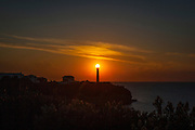 The power of solar: sunset glows above the top of Biarritz lighthouse - Phare de Biarritz, Pays Basque, France