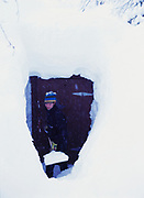 Timothy Bartling shoveling path to outhouse buried under twelve feet of snow, Winterlake Lodge, shore of Finger Lake, Alaska Range, Alaska.