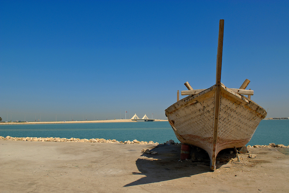 Bahrain - An old boat at the shore of Manama city, Sheikh Isa Causeway Bridge