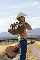 shirtless cowboy carrying a guitar and a duffel bag over his shoulder in rural New Mexico