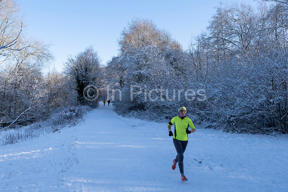 Man out running in a winter scene in the snow in Canon Hill Park in Moor Green on 25th January 2021 in Birmingham, United Kingdom. Deep snow arrived in the Midlands giving some light relief and fun during the current lockdown for people who simply enjoyed the weather.