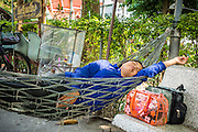 14 NOVEMBER 2012 - BANGKOK, THAILAND: A member of a passenger boat crew naps between runs at the Wat Sriboonreung Pier, the southern terminal of the Khlong Saen Saeb boat service. Bangkok used to be criss crossed by canals (called Khlongs in Thai) but most have been filled in and paved over. Khlong Saen Saeb is one of the few remaining khlongs in Bangkok with regular passenger boat service. Boats and ships play an important in daily life in Bangkok. Thousands of people commute to work daily on the Chao Phraya Express Boats and fast boats that ply Khlong Saen Saeb. Boats are used to haul commodities through the city to deep water ports for export.      PHOTO BY JACK KURTZ