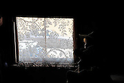 Two children (10 years old and 6 years old) in darkened room, beside lace curtain. Susannah Place Museum, The Rocks, Sydney, Australia