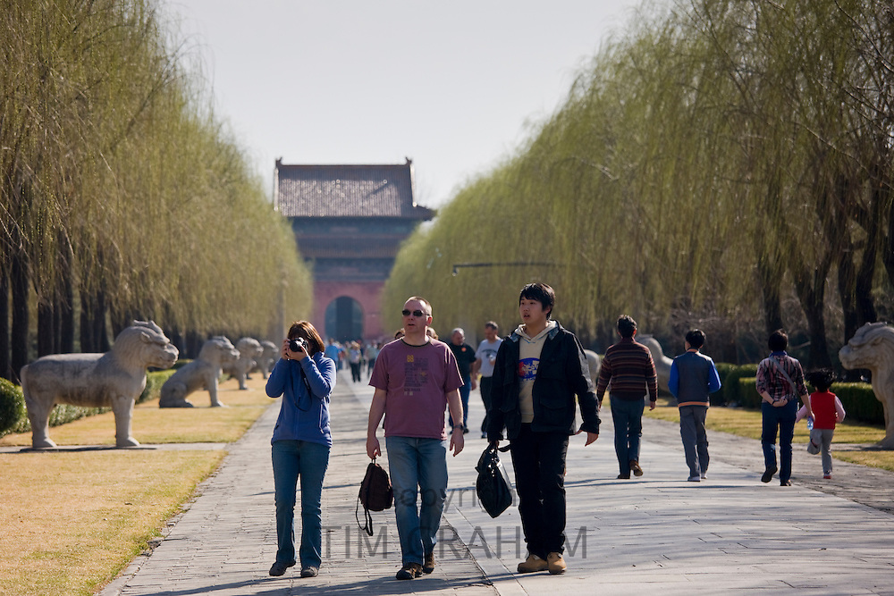 Western tourists with Chinese guide walk along the Spirit Way at the Ming Tombs site, Beijing, China