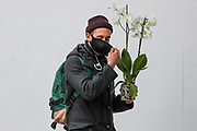A young man carrying a plant is covering his mouth prior to his entrance at Tottenham Court Road underground station in central London on Monday, May 11, 2020. <br />
