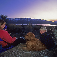 A family watches a sunset over the Sierra Nevada from a campsite near Crowley Lake in California.