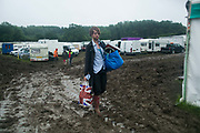 A man walks through mud ahead of the opening of the Glastonbury Festival 19th July 2016, Somerset, United Kingdom.  The Glastonbury Festival runs over 3 days and has 3000 acts, including music, art and performance and approx. 150.000 attend the anual event.