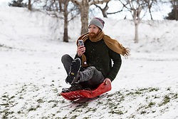 © Licensed to London News Pictures. 28/02/2018. London, UK. A sledger in Greenwich Park following heavy snowfall and sub zero temperatures overnight. The cold weather originating in Siberia has been dubbed 'the Beast from the East'.  Photo credit : Tom Nicholson/LNP