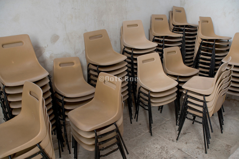 plastic chairs placed in the corner of a church