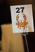 Table numbers decorated with smiling crabs show guests seating arrangements during the Milpitas Chamber of Commerce 21st Annual Auction & Crab Feed at Napredak Hall in San Jose, California, on March 7, 2014. (Stan Olszewski/SOSKIphoto)