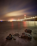 The River Severn and the Severn Bridge illuminated by light pollution reflecting from low clouds at night.