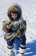 Alaska. Nome. Lela Oman in homemade parka doing a little ice fishing. PLEASE CONTACT US FOR DIGITAL DOWNLOAD AND PRICING.