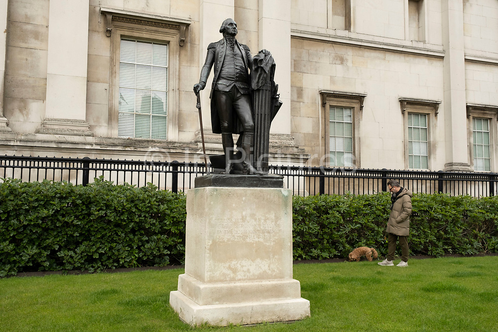 Statue of George Washington in a very quiet Trafalgar Square on 25th May 2021 in London, United Kingdom. A dog walker walks slowly behind the statue as his pet sniffs along the hedge line.