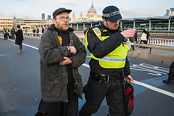 London, UK. 17th November, 2018. Police officers arrest a man after environmental campaigners from Extinction Rebellion blocked Blackfriars Bridge, one of five bridges blocked in central London, as part of a Rebellion Day event to highlight 'criminal inaction in the face of climate change catastrophe and ecological collapse' by the UK Government as part of a programme of civil disobedience during which scores of campaigners have been arrested.